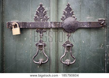 ancient door knockers, a metallic bar and a padlock on an ancient green wooden door
