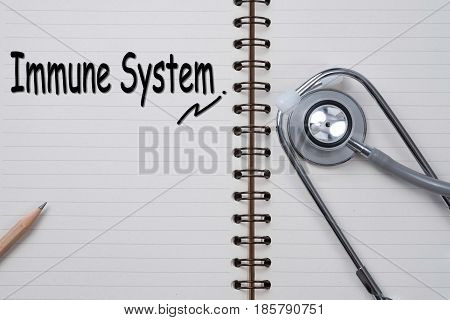 Stethoscope on notebook and pencil with Immune System words as medical concept