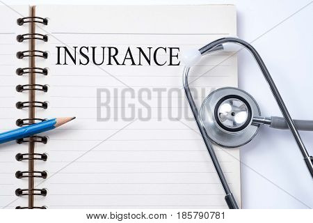 Stethoscope on notebook and pencil with INSURANCE words as medical concept.