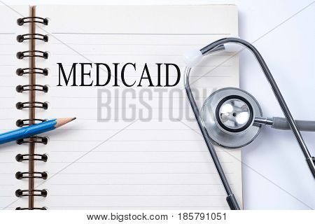 Stethoscope on notebook and pencil with MEDICAID words as medical concept