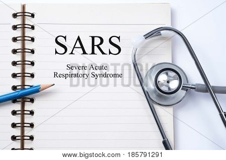 Stethoscope on notebook and pencil with SARS (Severe Acute Respiratory Syndrome) words as medical concept.