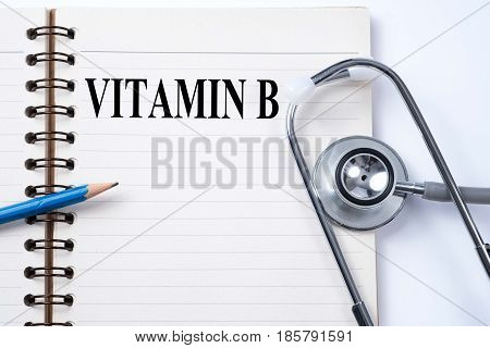 Stethoscope on notebook and pencil with VITAMIN B words as medical concept.