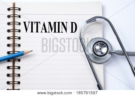 Stethoscope on notebook and pencil with VITAMIN D words as medical concept.