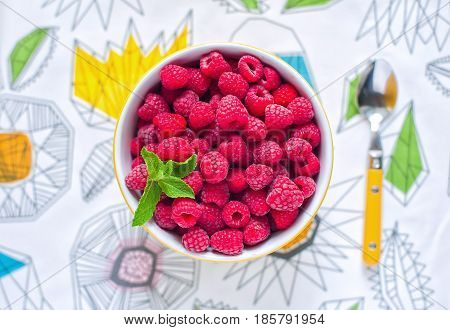 Raspberries in ceramic bowl. Top view. Ripe and tasty raspberries on a wooden background.