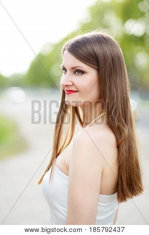 Young european woman in white dress with open shoulders standing outdoors. Portrait of beautiful caucasian girl on summer day
