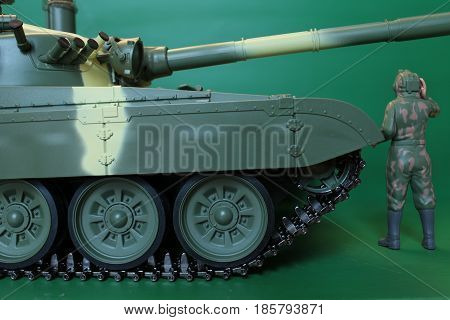 figure soldier in overalls and a helmet standing at battle tank