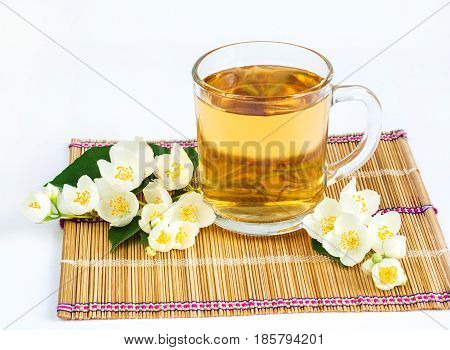 A cup of jasmine tea and jasmine flowers on a white background. Green tea. A refreshing and healthy drink. Selective focus.