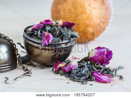 Close-up of tea strainer tea leaves and pink buds on a background of baked biscuit selective focus