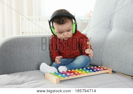Cute little baby with headphones and xylophone at home