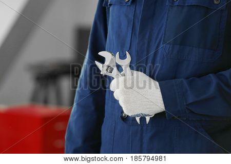 Auto mechanic with tools in car repair shop, closeup