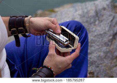 Man takes out the harmonic from the case. Hands Close-up.