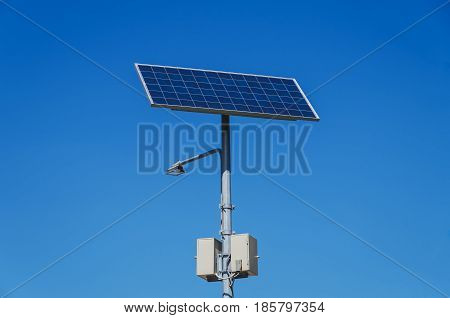 Lamp post with Solar photovoltaic powered on the background the blue sky
