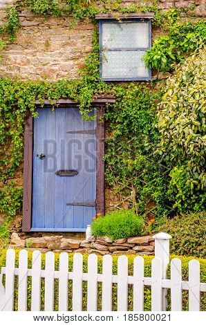 Entrance To A Country House, Blue Door And Small Window, White Fence, Plants On The Building, Stone