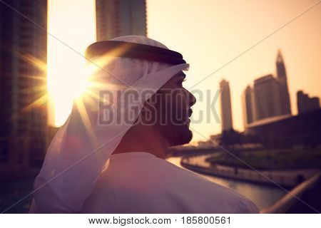 Arab man with kandura enjoying sunrise in Dubai proud of his country