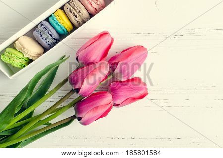 Pink flowers Tulips and gift box with macaroons on white rustic wooden table with place for text. Present on Mothers day Valentines Day or Womens day. Gritings woman concept. Top view. Copy space.