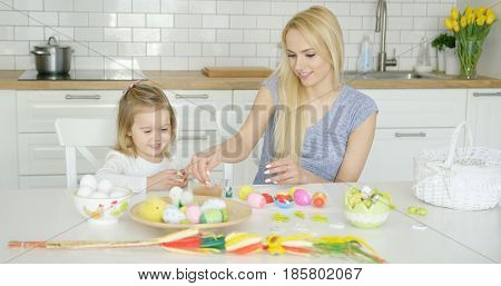 Attractive woman sitting at table with little girl and coloring Easter eggs together at light modern kitchen.
