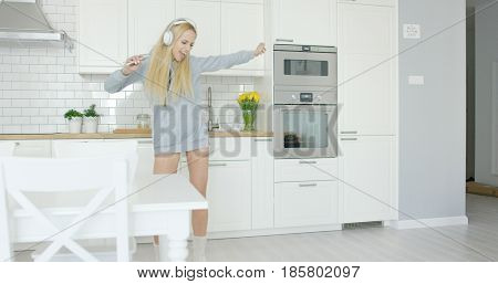 Beautiful young blonde wearing home clothing and listening to music with headphones and dancing in kitchen expressively.