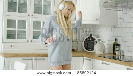 Beautiful and happy woman in sweat shirt using phone and listening to music with headphones and dancing.