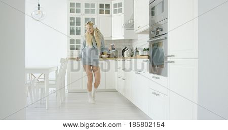 Young happy girl wearing home clothing and dancing expressively while listening to music with headphone in kitchen.