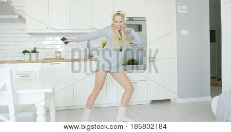 Beautiful young woman in sweat short dancing expressively while listening to music with headphones in kitchen alone.