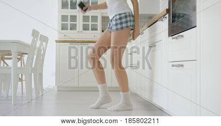 Crop faceless shot of woman in home shorts holding phone in hand and dancing in modern kitchen.