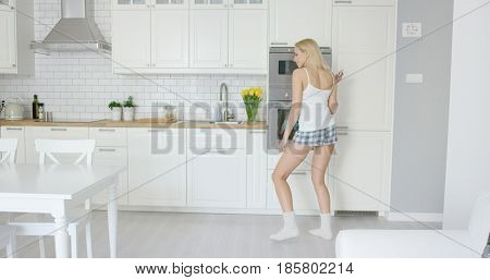 Back view of young woman in home clothing dancing alone in modern and light kitchen.
