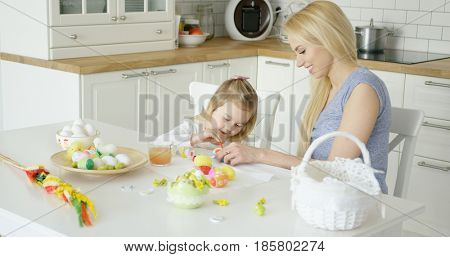 Little adorable girl and beautiful mother sitting at table at light kitchen and coloring Easter eggs together.