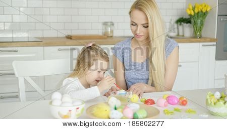Beautiful woman and little girl sitting by table and coloring Easter eggs together at modern light kitchen.