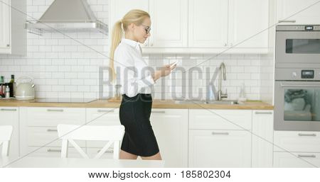 Side view of young attractive woman in formal clothing using smart phone while standing at modern kitchen.