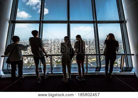 Tokyo, Japan - April 19, 2017: tourists at Tembo Deck observation deck. The Tokyo Skytree is a television broadcasting tower and landmark of Tokyo. Tokyo skyline and Sumida District.
