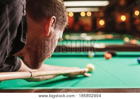 Man trying to hit the ball in billiard. Billiard room on the background.