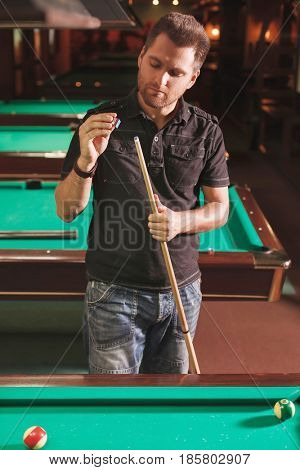 Man wipes a cue with chalk. Poolroom on the background.