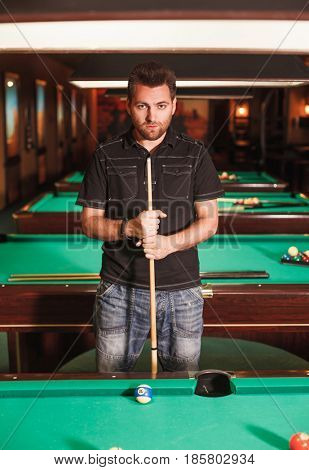 Concentrated player with a cue in billiard room. Playing billiards.