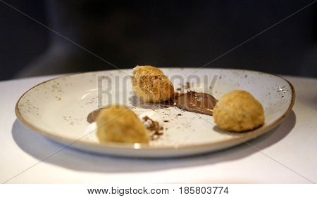 Cheesecake on the plate with chocolate cooked in liquid nitrogen. Molecular cuisine.