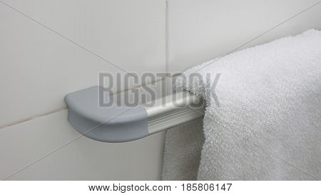 White towel hanging on a aluminum towel holder with a wall of white ceramic background
