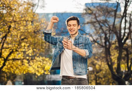 Young man standing outdoors holding mobile phone. He is full of joy because of receiving very important and good message. He is rejoicing lifting up one hand