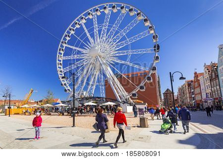 GDANSK, POLAND - MAY 2, 2017:  Ferris wheel over blue sky in Gdansk, Poland. Gdansk is the historical capital of Polish Pomerania with medieval old town architecture.