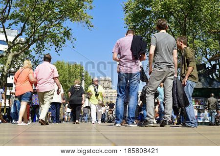 BARCELONA, SPAIN - APRIL 7, 2017: People walking by the upper section of La Rambla in Barcelona, Spain. Thousands of people walk daily by this popular pedestrian mall 1.2 kilometer-long