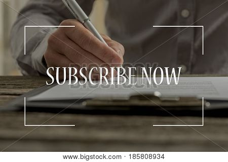 Subscribe now text over conceptual business scene with male hand signing contract or subscription form with a pen on a rustic wooden desk.
