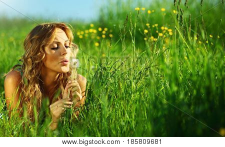 girl blow on dandelion on green field