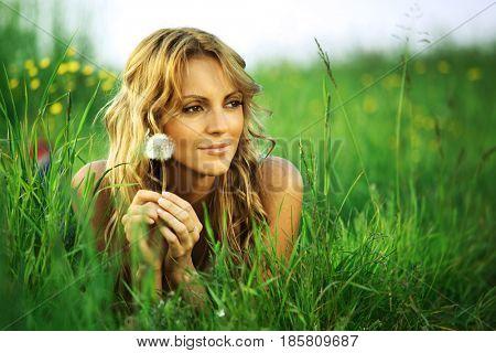 girl with dandelion on green field