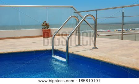 Corner of a swimming pool with marble border, blue ceramic walls and pool ladder with beach in background
