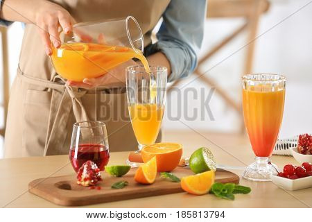 Woman preparing Tequila Sunrise cocktail in kitchen