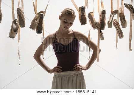 Attractive ballerina in a violet top and a cream skirt stands on the light background in the studio. Around her there are many hanging beige pointe shoes. She holds her hands on the waist.
