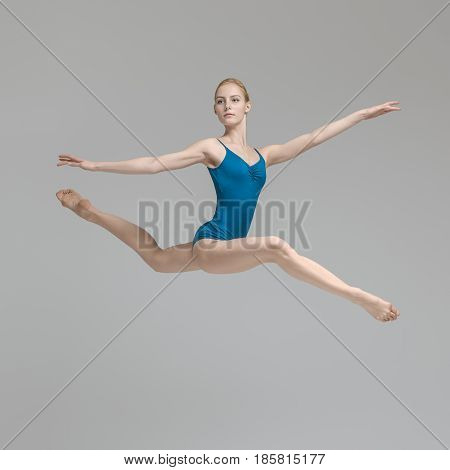 Incredible ballerina posing in the jump on the gray background in the studio. She wears a blue leotard and looks to the side. Her legs and arms stretched to the sides. Vertical.