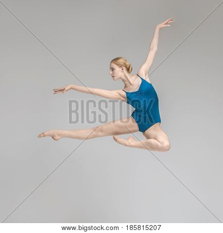 Delightful ballerina posing in the jump on the gray background in the studio. She wears a blue leotard. Her legs and right arm stretched forward, left arm stretched upward. Shoot from the side.