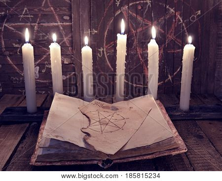 Magic book with pentagram and evil candles for occult ritual. Halloween background, black magic rite or spell, esoteric objects on witch table