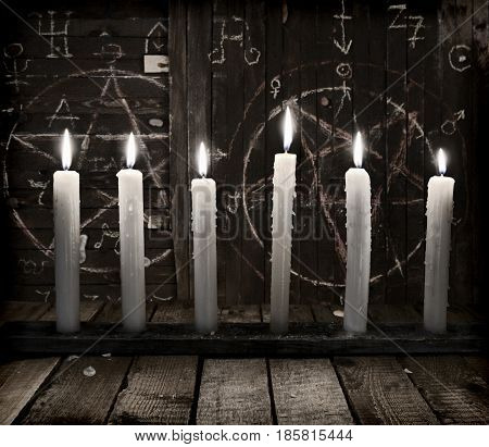 Still life with burning candles on wooden background with pentagram. Halloween background, black magic rite or spell, occult and esoteric objects on witch table