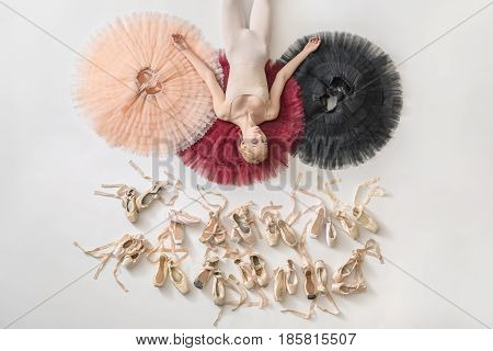 Gorgeous ballerina lies on the colorful tutus on the white floor in the studio. She wears light dance wear. Below her there are many pointe shoes. Tutus are peach, burgundy and black. Top view photo.