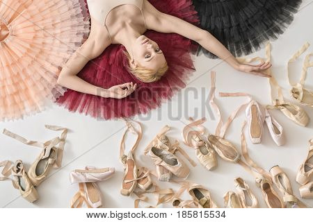 Pretty ballerina lies on the colorful tutus on the white floor in the studio. She wears a light top. Below her there are many pointe shoes. Tutus are peach, burgundy and black. Closeup. Horizontal.